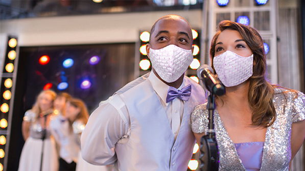 A young man in a bow tie and a young woman wearing matching masks sing into a microphone with a trio singing into a microphone in the background