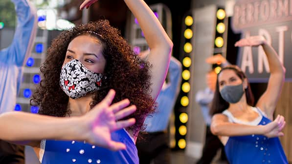 A woman with long, curly hair wearing a Minnie Mouse mask dances in a group of several dancers