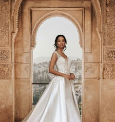 Bride in wedding dress under an archway with mountains in the background.